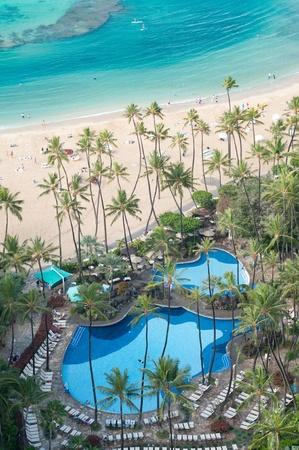 sun s: Piscina tropicale circondata da palme accanto alla spiaggia di sabbia