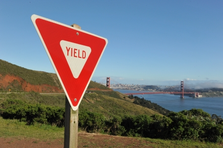 yield sign: Yield sign with Golden Gate Bridge and San Francisco skyline in the background