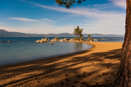 Stars in the sky at Lake Tahoe with boulders in a bay photo