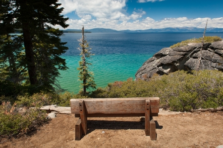 Old wooden bench looks over Lake Tahoe Stock Photo