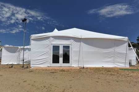 White tent with glass doors in a field