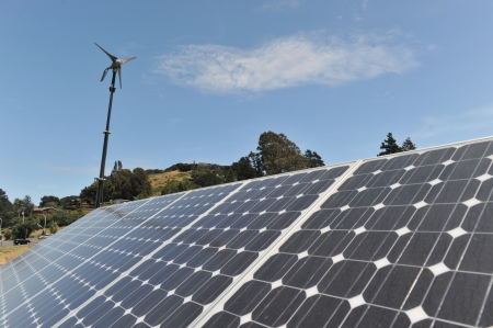 l petrol: Una h�lice est� por encima de algunos de los paneles solares con el cielo azul y algunas nubes