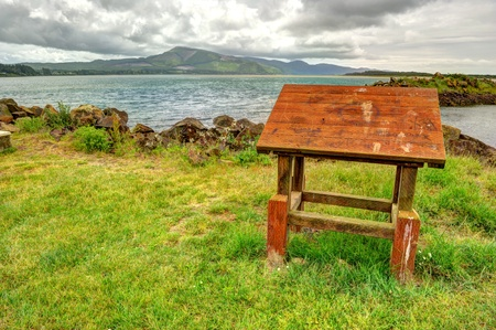 A wooden podium in a grass field by a bay of the Pacific Ocean