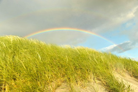 A double rainbow arches over a grassy hill