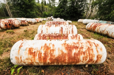 rusting: Rows of gas storage tanks lay in a field rusting Stock Photo