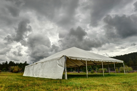 Storm approaches a tent in grass field