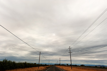 telephone: A country road has telephone poles and wires on both sides Stock Photo