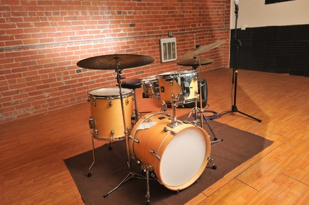 Drum set  in a brick walled studio on a rug with wood floor