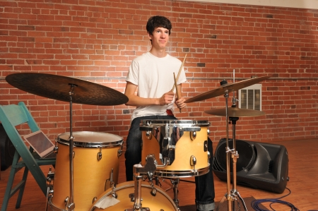 Drummer playing drums in a brick walled studio with computer on chair Stock Photo