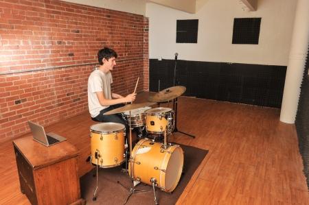 Batterista a suonare la batteria in uno studio con pareti in mattoni con il computer sulla sedia Archivio Fotografico - 21264677