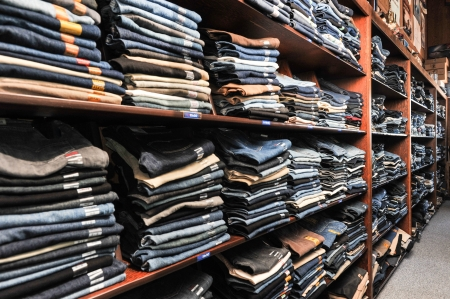 Rows of denim jeans on shelves in a retail store