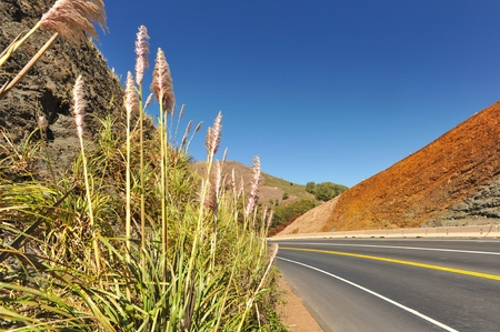 curving: Hill with different color minerals next to a road curving by