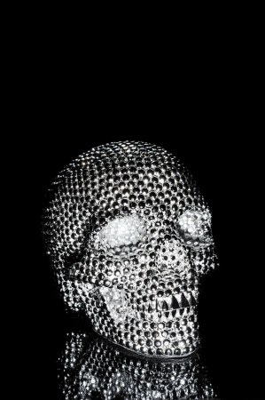 A metal skull with many reflective dots on a black  photo