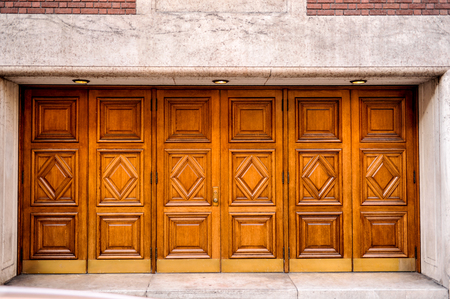 private access: Doors to a building are old wooden with one door handle Stock Photo