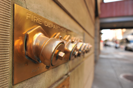 capping: A set of fire hose conections on the wall of a building Stock Photo