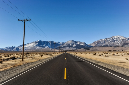 telephone poles: Single yellow line in middle of road leading to the mountains with telephone poles on one side