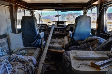 Old recreational vehicle filled with dirt and crap with cracked windows