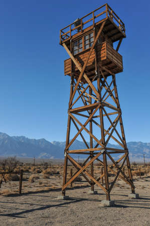 Guard tower with a search light in the desert by the mountains photo