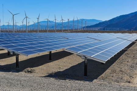 Rows of solar panels and wind turbines capture the sun and wind