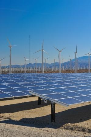 Righe di pannelli solari e turbine eoliche catturano il sole e il vento Archivio Fotografico - 25477266