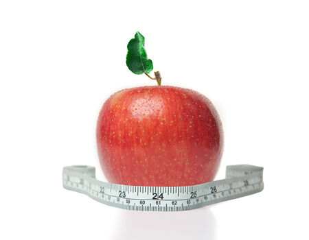 Close-up of a red apple with a measuring tape around it