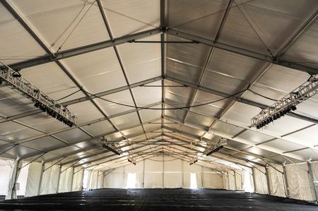 Grande tenda bianca con pavimento nero e travi e l'illuminazione pronti per una festa Archivio Fotografico - 27952713
