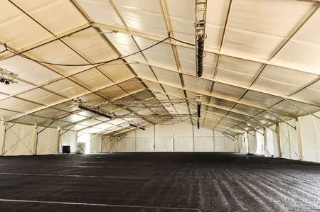entertainment event: Large white tent with black floor and rafters and lighting ready for a party