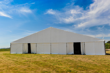 A huge tent in a grass field under sunny sky