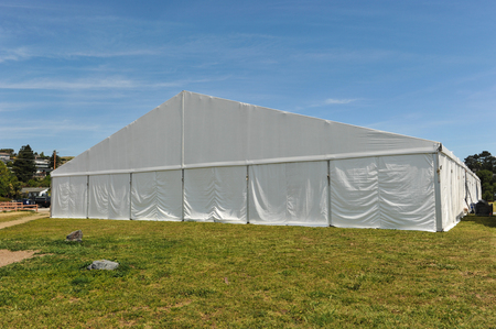 A huge tent in a grass field under sunny sky photo & Large White Tent With Black Floor And Rafters And Lighting Ready ...