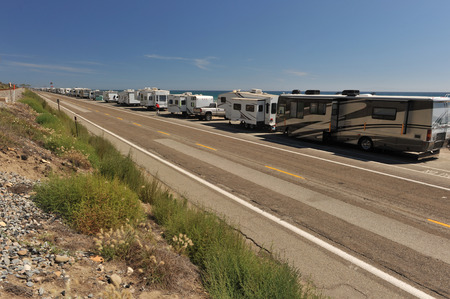 A row of RVs are parked alongside of a road near the Pacific Ocean