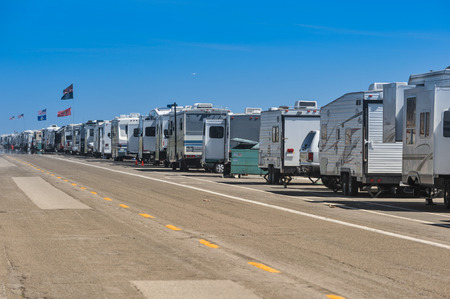 A row of RV's are parked alongside of a road near the Pacific Ocean