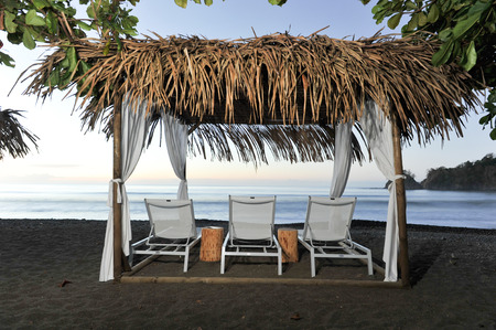A palm fron covered cabana with three lounge chairs Stock Photo
