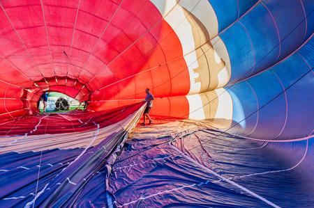 Colorata mongolfiera dall'interno con un uomo che tira il pallone Archivio Fotografico - 36876184