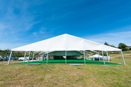A large tent in a grassy field is being constructed for a party