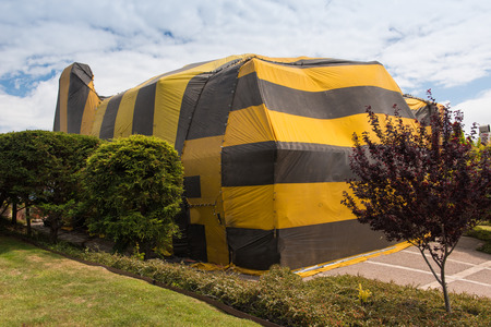fumigation: Brown and yellow striped tent covers a house for fumigation process Stock Photo