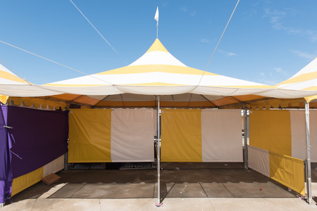 Canopy tent set up outdoors with flag on top is empty