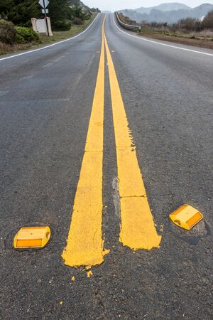 reflectors: Close up of road reflectors and double yellow lines on a road going up a hill