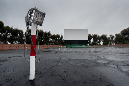 Parking area for a drive in movie with screen and speaker poles