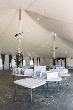 A large white tent iwith tables and chairs for parties and enteraining