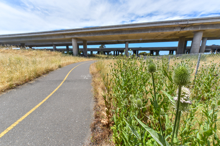 A trail for walking next to a freeway with fence.