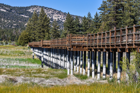 A wooden walkway bridge over Big Bear Lake with rails when the lake is 14 feet below normal