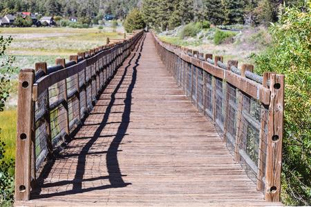 bear lake: A wooden walkway bridge over Big Bear Lake with rails when the lake is 14 feet below normal