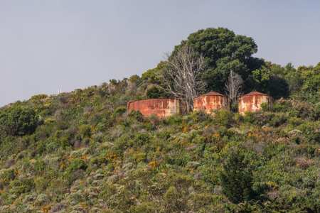 Three rusty water tanks on the side of a hill.