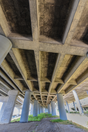 Pillars hold up an expressway overpass as seen from underneath