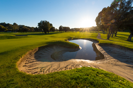 ploy: A bunker is half full of water after a storm next to a green Stock Photo