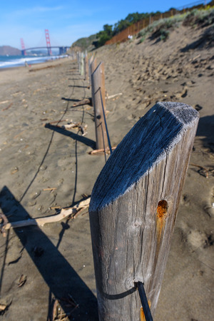 A cable and wood fence on the sand at Baker Beach by the Golden Gate Bridge 版權商用圖片