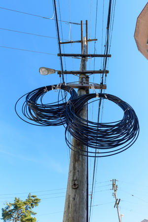 Additional wire hangs on a telephone pole in two circles