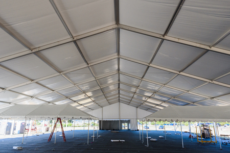 Inside of a large white tent in a grass field for parties and entertaining Stock Photo
