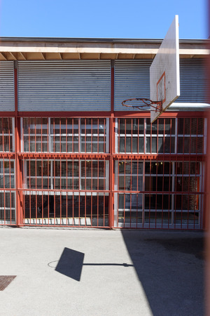 A court for playing basketball is surrounded by metal bars and a building