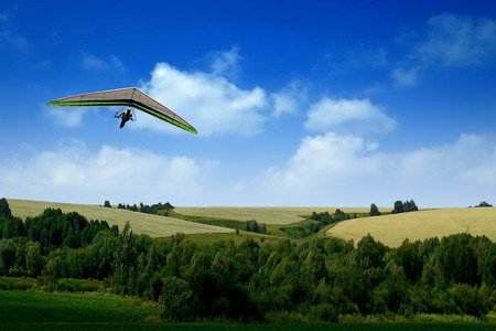 trave: Glider flying in the sky above the green meadows. Stock Photo